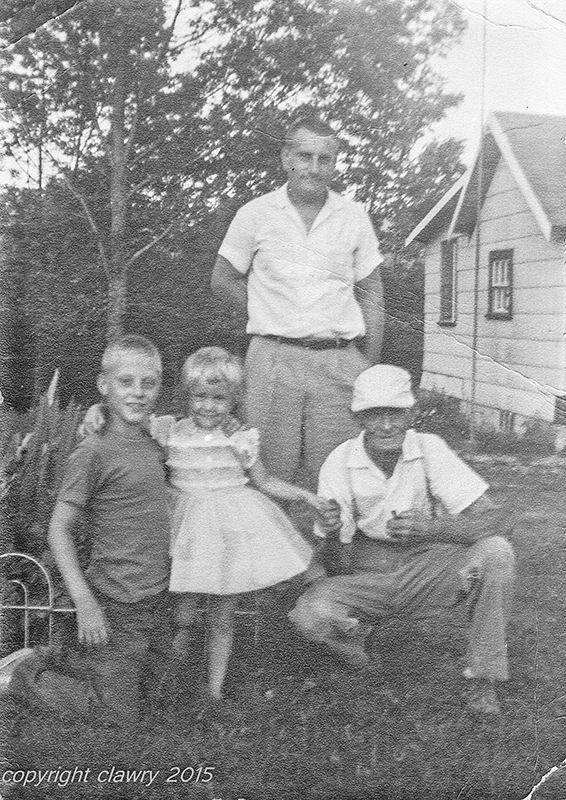Left to right: Philip Lawry, Cynthia Lawry, David Lawry, Chester Walls, taken about 1961. The house in the background belonged to Ida Walls Seeley, one of Chester & Myrtle Walls' daughters. Photo courtesy of Cynthia Lawry